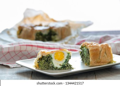 """Two slices of """"Torta pasqualina"""" pie. Background: the pie and a napkin."""
