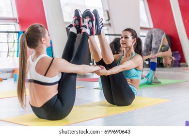 Two slim young girlfriends sitting in buddy boat pose also called navasana practicing yoga together in gym