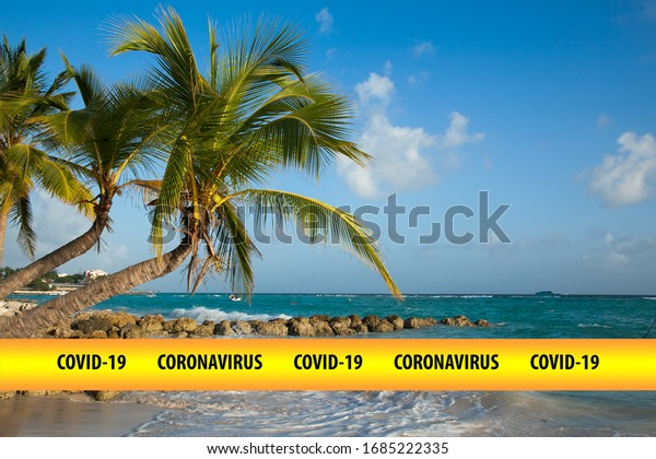 """Two sloping palm trees  are on the beach by the sea at sunset. In the foreground text element is """"Covid-19 Coronavirus"""".  The concept of closed beaches in the period of quarantine"""