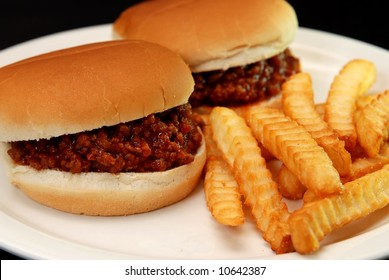 Two sloppy joe burgers and crinkle cut french fries isolated on black background.