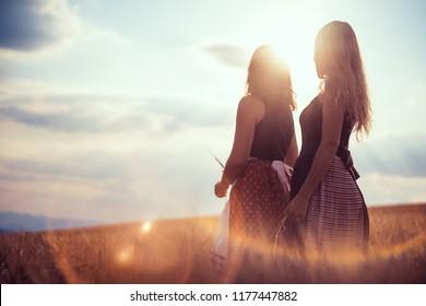 Two Slovak Folk woman standing on a golden field. She is wearing traditional Eastern Europe Slavic folk costumes.