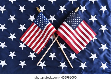Two small American flags crossed on the star field of a larger flag. Perfect for Fourth of July or other patriotic American holidays.