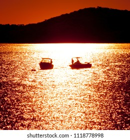 Two small boats silhouetted in front of reflections of setting sun, Stanage, Queensland, Australia.