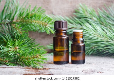 Two small bottles with essential pine oil (extract, tincture, infusion). Old wooden background. Aromatherapy, spa and herbal medicine concept. Copy space.