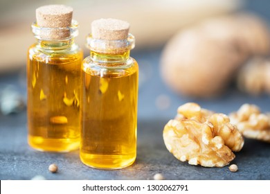Two small bottles of walnut oil and walnuts close up.