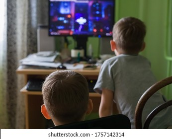 Two small boys are looking at the computer screen, sitting on chairs at home. The view from the back.