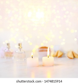 Two small candles with light yellow spots on light background