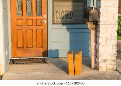Two small cardboard boxes sitting on doorstep of home business in small town America . Package delivery , cardboard boxes left on patio doorstep during morning sunshine