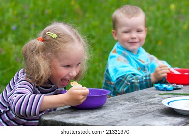 Two small children eating at the table outdoors