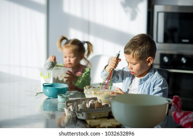 Two small children prepare something from the dough. A boy and a girl are sitting at the kitchen table. Their faces are stained with flour. Children try hard.