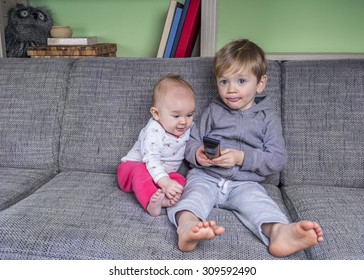 Two small children watching television on the couch