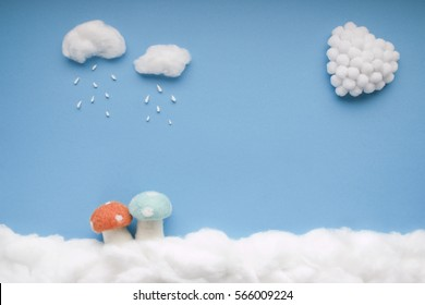 Two small clouds pouring rain over two mushrooms and a white heart, in a heavenly scenery where the clouds  are made from cotton-wool, on a blue sky paper background.
