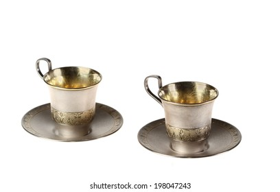 Two small cups coffee with saucers. Gold covering. Isolated