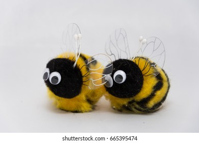 two small cute bumble bee plush toys in a white background