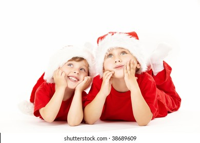 Two small dreaming boys lie in caps of santa, isolated