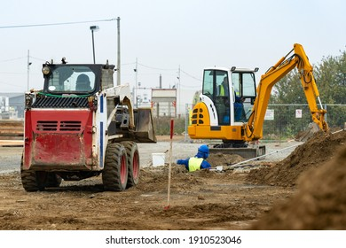 Two small excavators digging a trench on a construction site. Worker laying pipes in a trench.