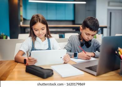 Two small friends writing homework , using smart digital tablet at modern blue classroom.