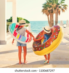 Two small girls with inflatable toys on the beach. Summer vacation and traveling concept