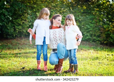 Two small girls with mother in autumnal park