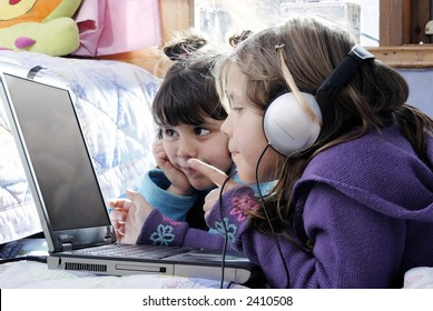 two small girls, one with laptop and headphones pointing at the screen and the other watching it