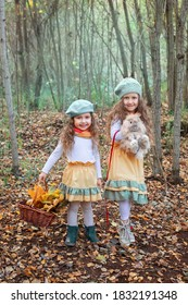 Two small girls are walking in fall forest with rabbit and hand basket
