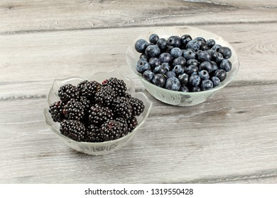 Two small glass bowls, one with blackberries, other blueberries, on gray wood desk.