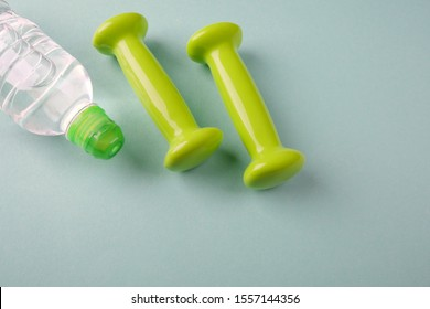 Two small green weights and a bottle of water on a light turquoise