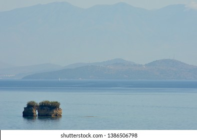 Two small isalnds stand along in a bay. Bushes cover the top of them. The water is calm. Hills and mountains are in the distance.