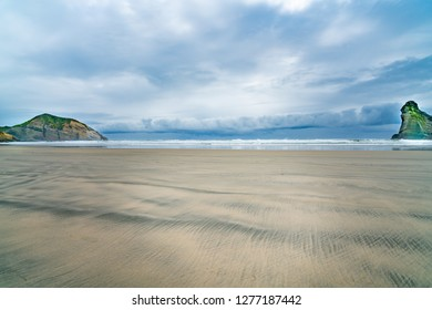 Two small islands on Wharariki Beach on overcast day at low tide in moody atmospheric image