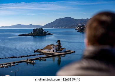 Two small islands, Vlaherna and Mouse Island with Christian churches in Corfu, Kerkyra, Greece, sunny spring day view from high above with blurred silhouette of man and blue waters Ionian Sea