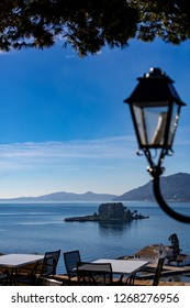 Two small islands, Vlaherna and Mouse Island with Christian churches in Corfu, Kerkyra, Greece, sunny spring day view from high above with blurred street lamp decoration and blue waters Ionian Sea