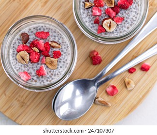 two small jars of vanilla chia pudding topped with freeze dried strawberries and dark chocolate on bambu plate