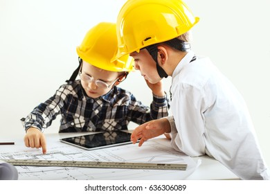Two small kid boys with yellow hardhats and examining blueprint.