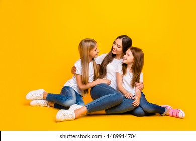 Two small ladies communicating with beautiful babysitter sitting floor wear casual white t-shirts isolated yellow background