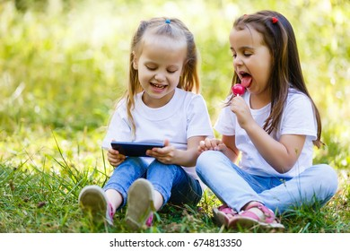 Two small laughing girls sit together at the outdoor in the city and play with smartphone