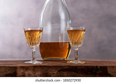 Two small liqueur vintage glasses with a bottle on a wooden table and with a blurry abstract background