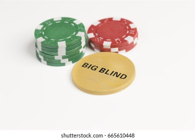 Two small piles of gaming chips behind the big blind token isolated against a white background