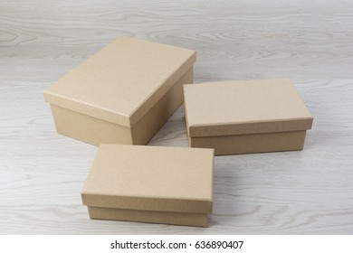 Two small raw plain boxes for small items on white wooden background. With shadow.