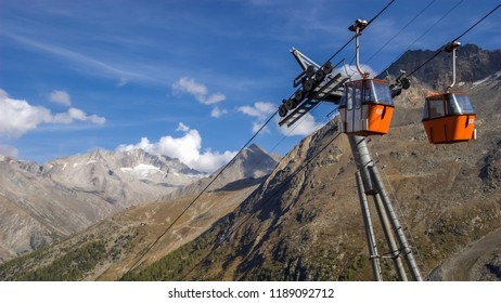 Two small red cable car cabins against the backdrop of the gorgeous mountains near the village of Saas-Fee, the main village in the Saastal, or the Saas Valleyin the canton of Valais in Switzerland.