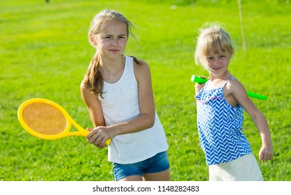 Two small sisters having fun together outdoors playing in badminton
