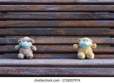 Two small Teddy bears sitting apart on gray bench outdoors, having facemasks on. Physical distancing concept.