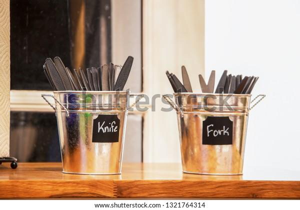 プラスチック製の刃物を持つレストランのカウンターの上に2つの小さなスズバケツ – ナイフとフォーク – 大胆なブロック背景に限定フォーカス