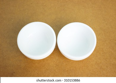 Two small white cup on wooden background