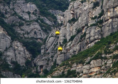 Two small yellow cabins of Montserrat aerial cable car transport people to old monastery near Barselona. Breath taking journey over the Llobregat River and Valley, village of Monistrol and  Santa Cove