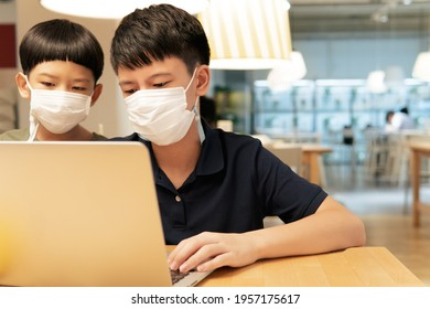 Two smart Asian brother kids with face mask video call with computer laptop in cafeteria. Online learning and social distancing during Covid-19 pandemic. 5G internet technology.
