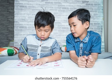 Two smart casual Kids discussing over work book at home. Asking for tutoring in practice. Education concept.