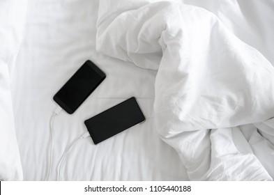 Two Smart phone is charging on the white bed