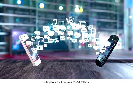 Two smart phones exchanging messages represented as flow of social media related icons. Blurred city background.