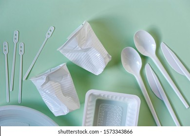 Two smashed white plastic coffee cups, spoons, knives, stirrers, plate and box on a light green background with soft shadows.  Zero waste, plastic free, stop pollution, ecological concept.