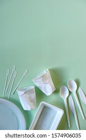 Two smashed white plastic coffee cups, spoons, knives, stirrers, plate and box on a light green background with copy space. Zero waste, plastic free, stop pollution, ecological concept. Vertical image